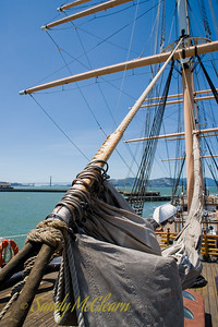 The view from the bow (looking aft) of the sailing ship Balclutha, built in Scotland, and now restored and on display in San Francisco at the Hyde Street pier. The Golden Gate Bridge is in the background.