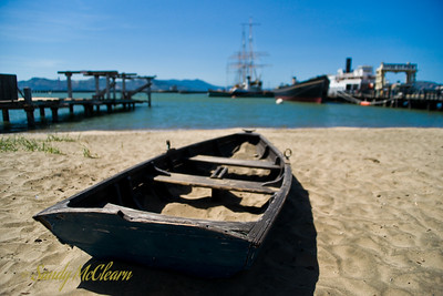 A rowboat sits on the beach in front of the Hyde Street Pier. The collection of ships in the background are mostly open to the public.
