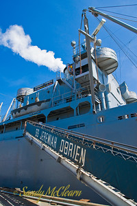 The S.S. Jeremiah O'Brien is one of only two restored and operational Liberty ships left over from the Second World War. She is shown here with steam issuing forth from her funnel, as she still has steam up from her trip out of drydock earlier in the morning.