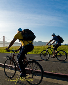Two cyclists in Crissy Field with the Golden Gate Bridge in the background.