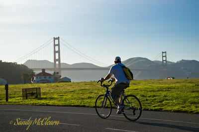 A cyclist in Crissy Field with the Golden Gate Bridge in the background.