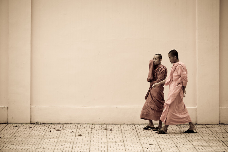 Two monks stroll along a walking only street next to the palace in Phnom Penh.