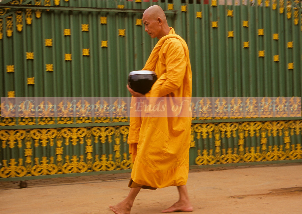 Monk on daily ritual route to collect his meager meal for the day in begging bowl
