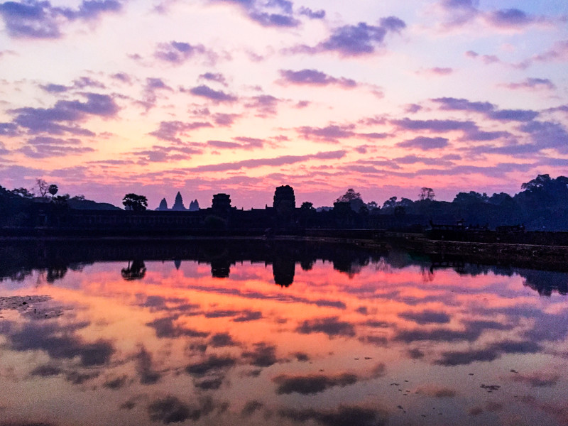 Sunrise at Angkor Wat temple complex, Siem Reap, Cambodia<br /> <br /> Angkor, in Cambodia's northern province of Siem Reap, is one of the most important archaeological sites of Southeast Asia. It extends over approximately 400 square kilometres and consists of scores of temples, hydraulic structures (basins, dykes, reservoirs, canals) as well as communication routes. For several centuries Angkor, was the centre of the Khmer Kingdom. With impressive monuments, several different ancient urban plans and large water reservoirs, the site is a unique concentration of features testifying to an exceptional civilization. Temples such as Angkor Wat, the Bayon, Preah Khan and Ta Prohm, exemplars of Khmer architecture, are closely linked to their geographical context as well as being imbued with symbolic significance. The architecture and layout of the successive capitals bear witness to a high level of social order and ranking within the Khmer Empire. Angkor is therefore a major site exemplifying cultural, religious and symbolic values, as well as containing high architectural, archaeological and artistic significance.