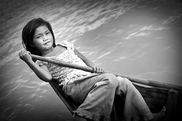 Small girl maneuvering her boat on a canal next to Tong Le Sap lake