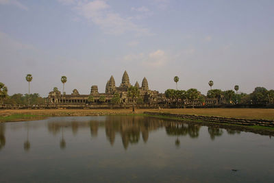 Angkor Wat. The outer enclosure, 1025 by 802m, is surrounded by a moat 190m wide. Access to the temple is by an earth bank to the east and a sandstone causeway to the west; the latter, the main tourist entrance, is a later addition, posssibly replacing a wooden bridge.