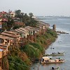 Restaurants and houses cling to the Mekong riverbank on stilts.