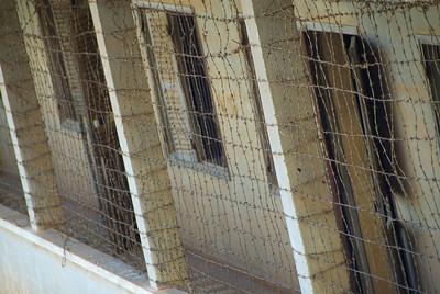 Barbed wire covers the balcony at the Tuol Sleng (S-21) Genocide Museum - Phnom Pehn, Cambodia