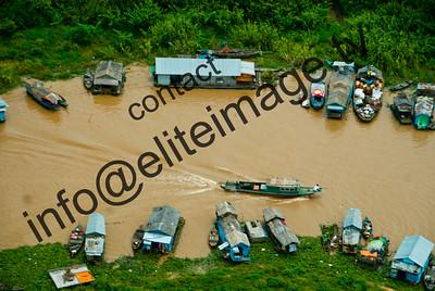 A boat makes it way amongst houseboats on lake Tonie Sap near Siem Reap