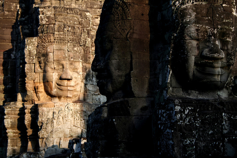 3 colossal stone faces at sunset, Bayon Temple, Angkor.