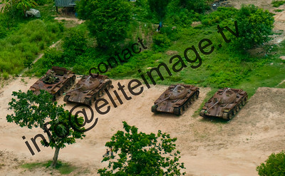 Obsolete russian tanks lay dormant in a Cambodian field, aerial view.