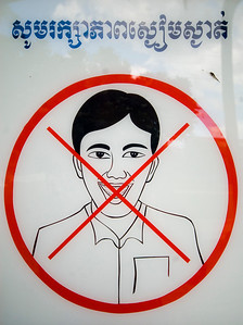 A sign and warning against laughing or smiling whilst visiting the Tuol Sleng (S-21) Genocide Museum - Phnom Pehn, Cambodia
