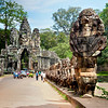 City Gate entrance to Angkor Thom.  The structure lining the bridge represents a gigantic cobra with figures riding on his undulating back.