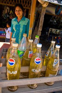 Streetside stall selling petrol in soft drink bottles - Phnom Penh, Cambodia
