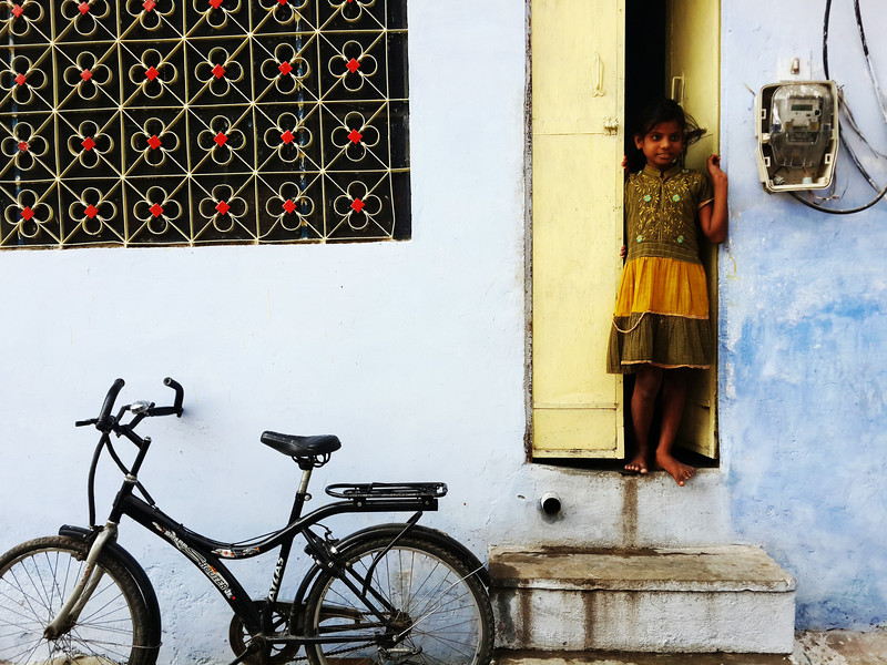 A girl looks out her front door in Jaipur.