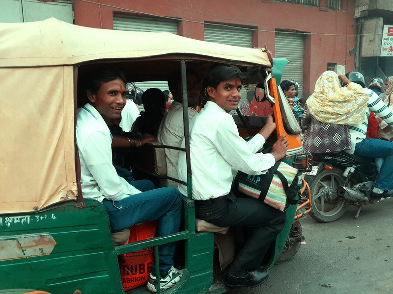 A tuk tuk of shy young men passes by during rush hour traffic in Agra.