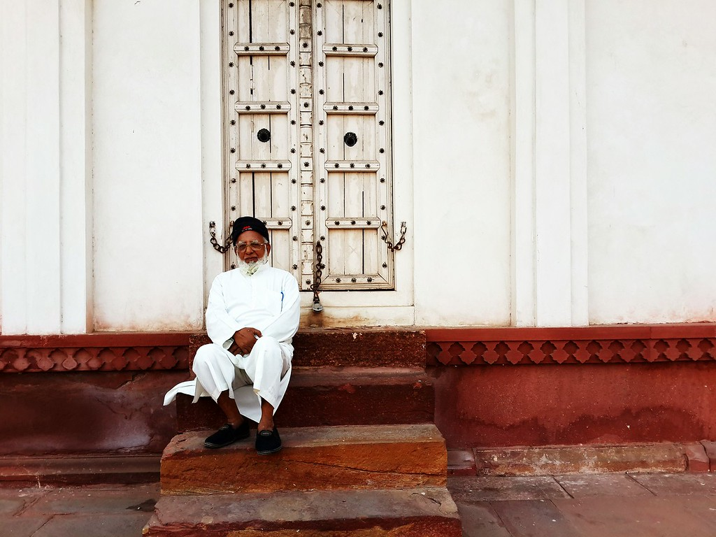 A man waits in a doorway for his grandson to return
