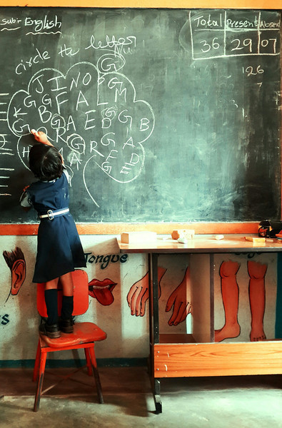 A student standing on a chair circles the letter G in a classroom at the Good Shepard School in Uddamarry