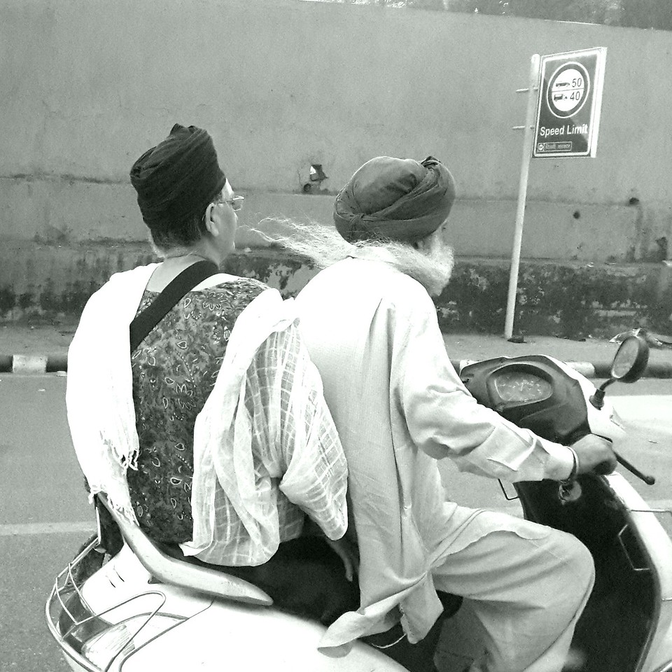 And old man's white beard flows with the wind as he powers his scooter through the chaotic Indian traffic system.
