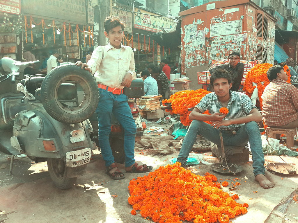 Young men at a street market in New Delhi wait to sell more orange flowers as Diwali decorations.