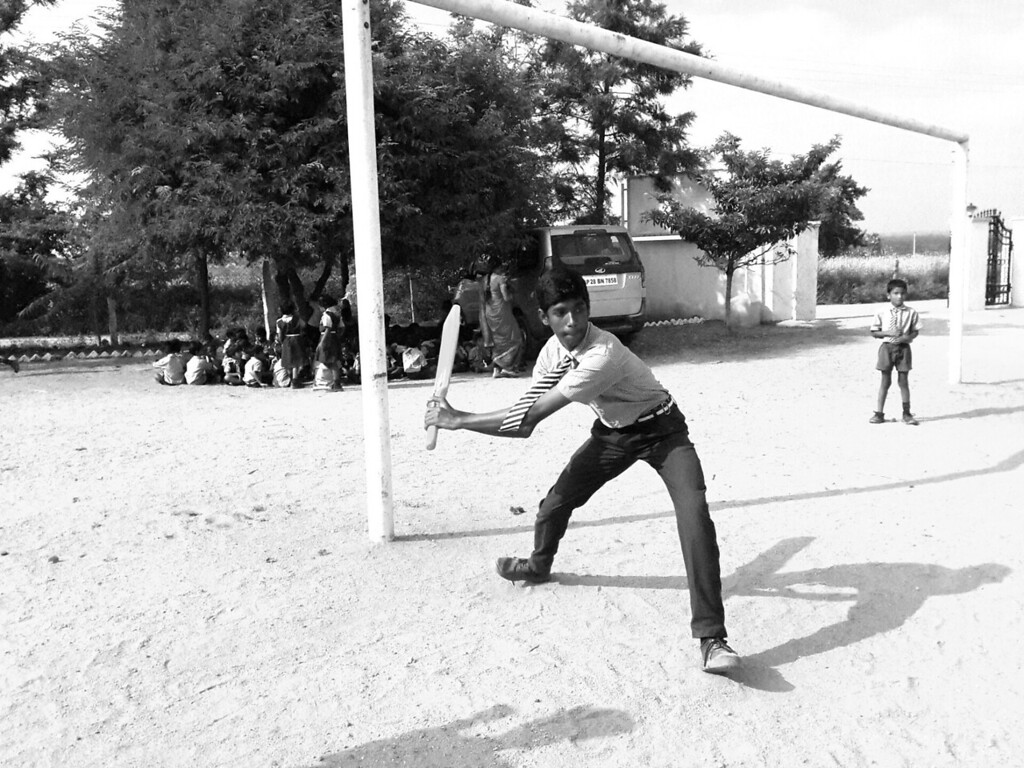 A boy swings the Cricket paddle in the large playground at the Good Shepard School in Uddamarry.