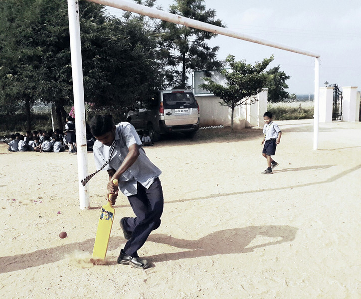 A boy swings the Cricket paddle in the large playground at the Good Shepard School in Uddamarry