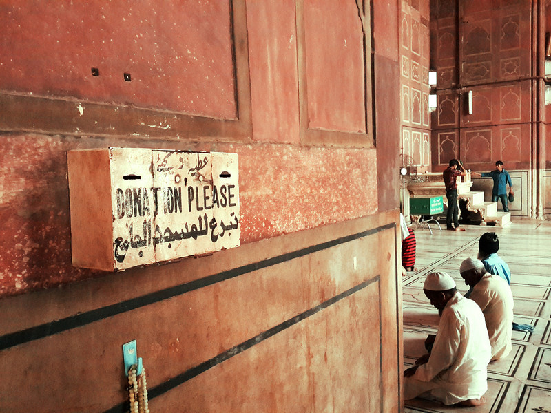 A sign asks for donations as Muslim men pray in India's largest Mosque, Jama Masjid