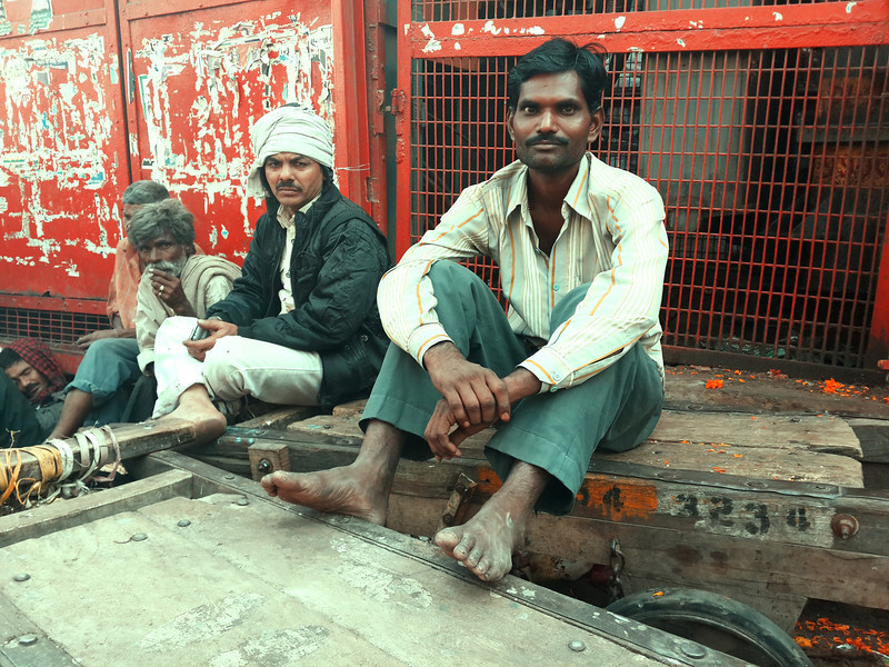 A group of men chat while sitting at a street market in Old Delhi.