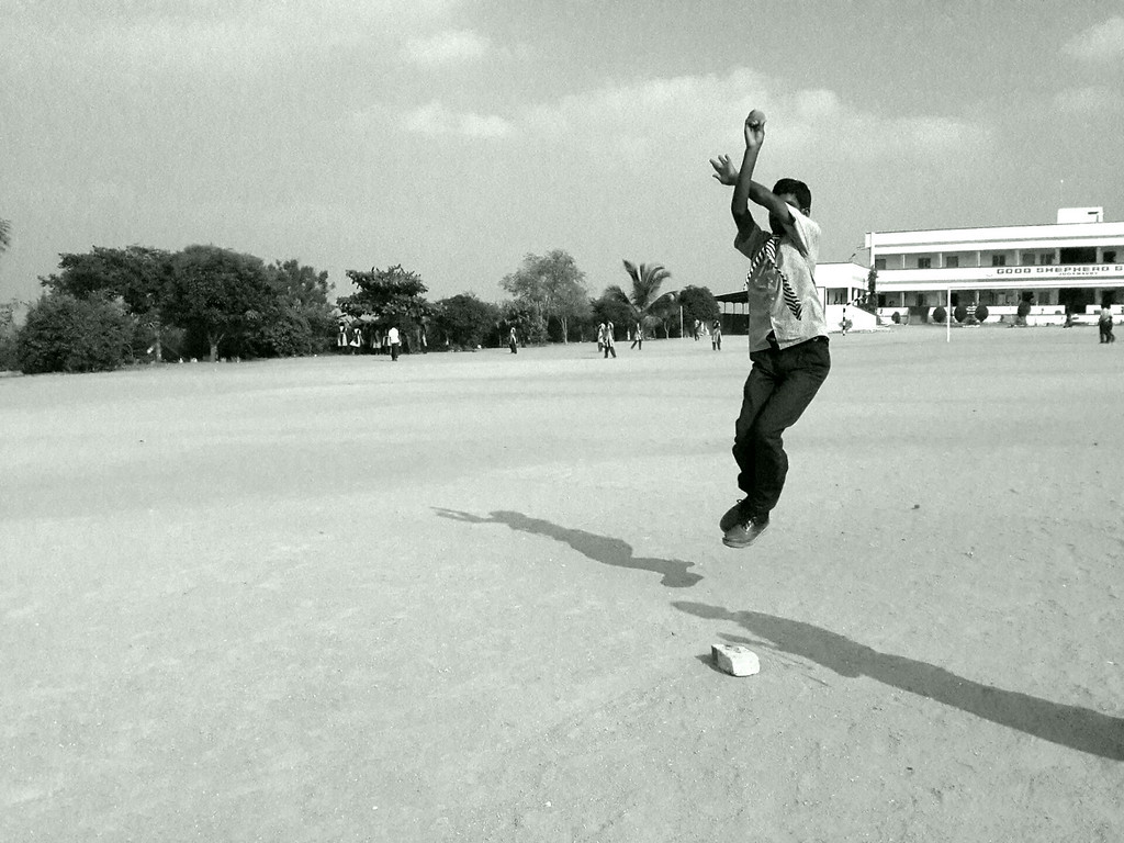 A boy winds up to throw his Cricket pitch.