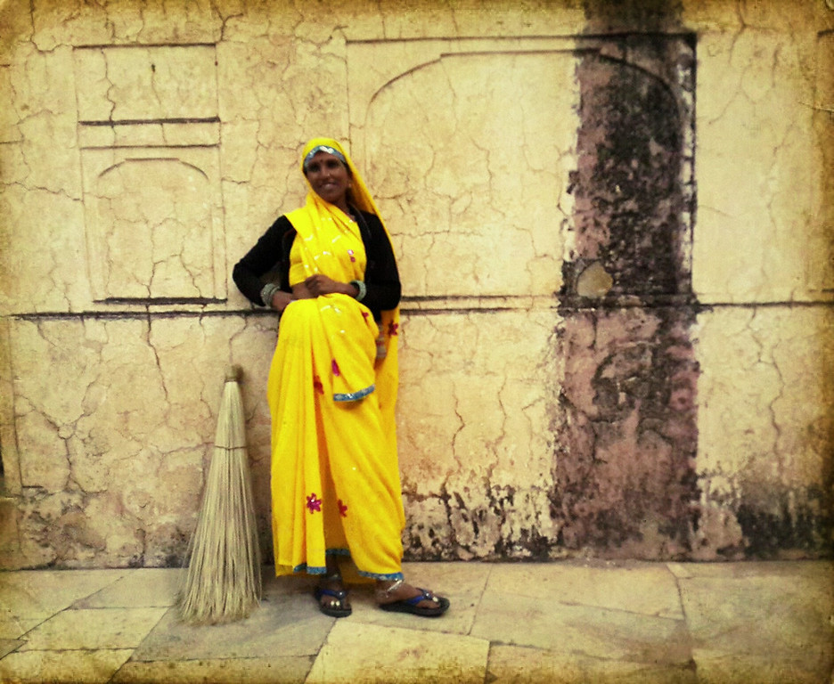 A woman sweeps the grounds of the Jaipur fort.