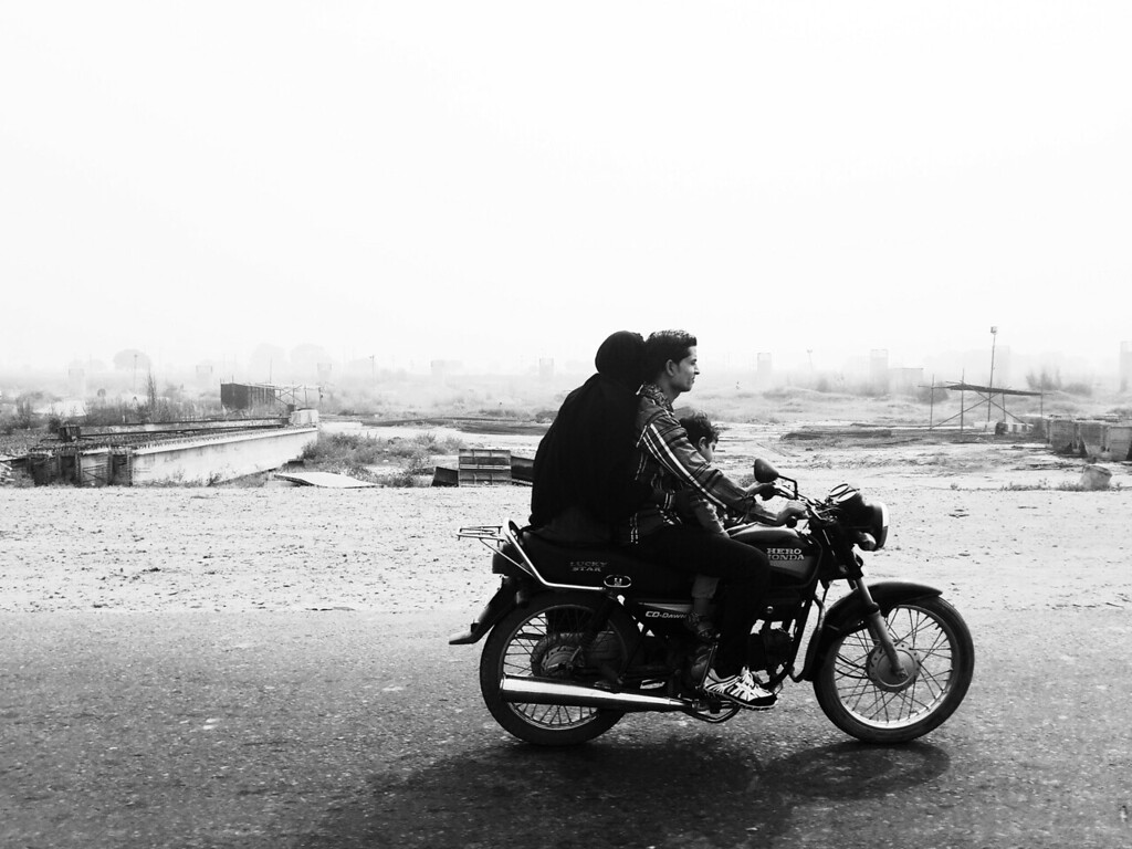 A family that rides together, stays together. A family rides on their motorbike on the highway in the countryside.