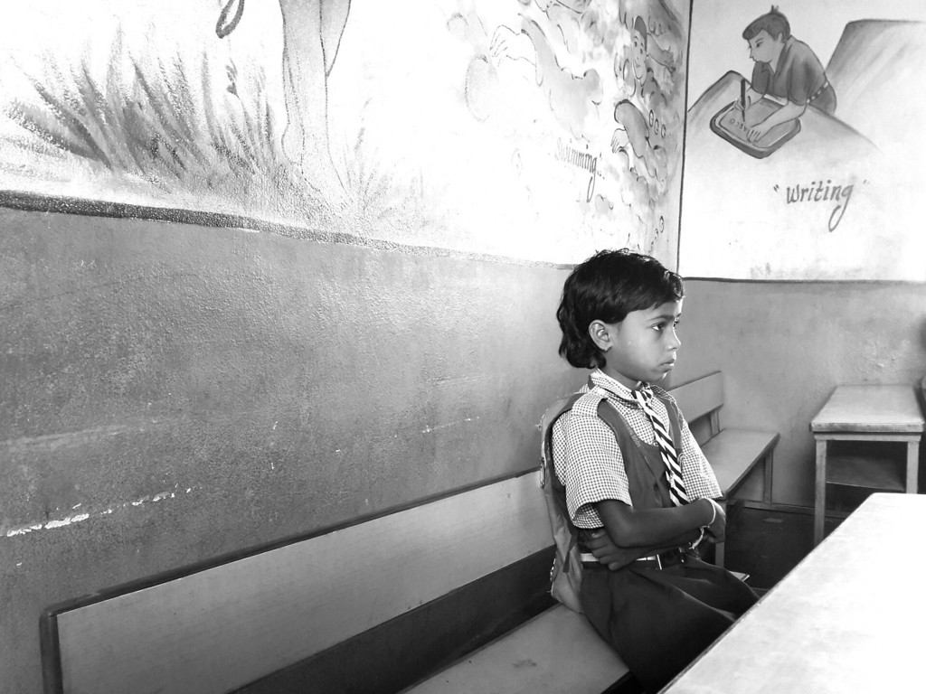 A girl listens to the teachers lecture in the back of the classroom at Good Shepard School in Uddamarry.
