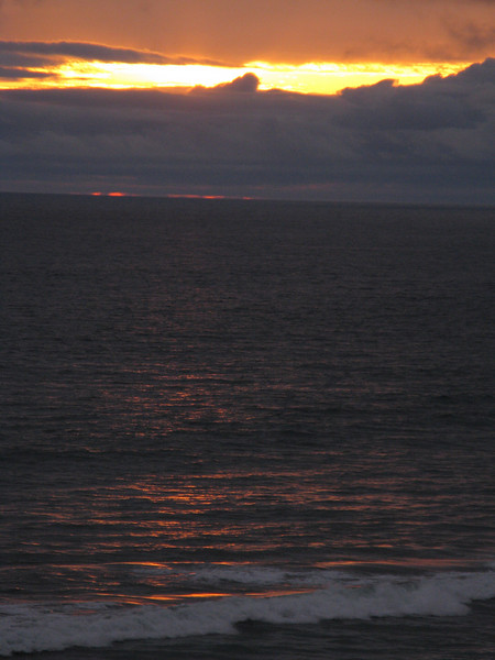 Sun obscurred by heavy marine layer. Just a sliver of red on the horizon.