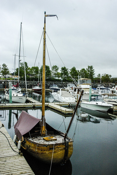 Lovely old small sloop with spar and deck cover.