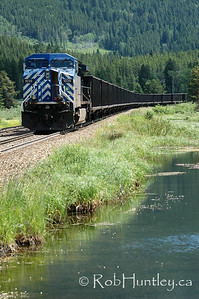 Freight train alongside a stream in southern British Columbia.