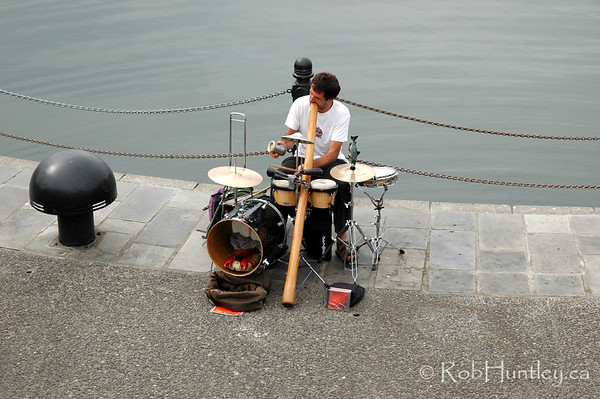 Musician on the street. Busking with drums and didgeridoo ..