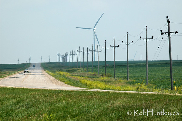 Rural road with windmills looming in the distance in agricultural southern Manitoba. © 2006 Rob Huntley