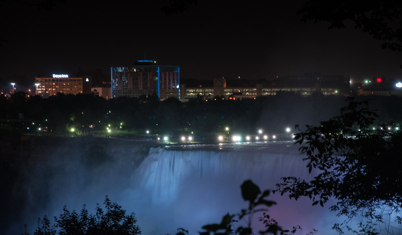 The American Falls at night with Niagara Falls USA in the distance.