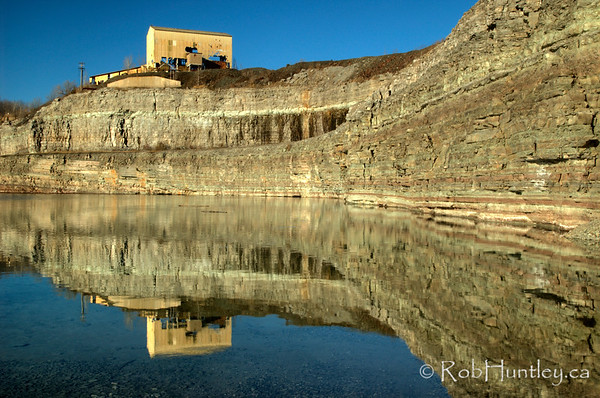 Reflection in the water-filled mine with limestone walls and a derelict building at the Marmora Iron Mine, Marmora, Ontario. HDR - high dynamic range (3 exposures mapped into one).  © Rob Huntley