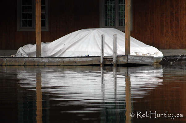 Boat under cover. Boat protected from the weather under the carport-like boathouse adjacent to a cottage on Lake Joseph in the Muskokas. © Rob Huntley