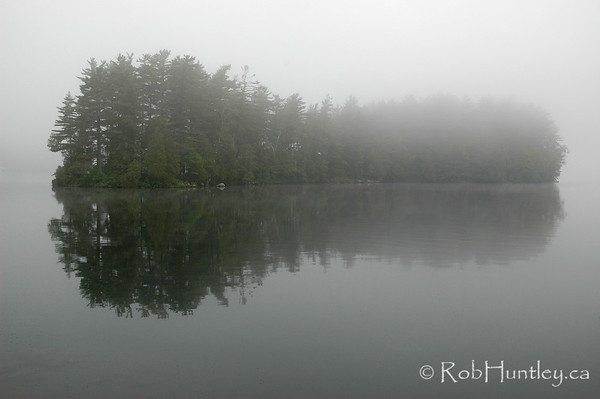 Island in the mist at sunrise on Lake Joseph in the Muskokas.