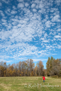 "Autumn Country Sky Woman in a red coat. Late fall sky while on a hike in the country. Ottawa Valley. Not for sale on this website. It is a ""similar"" to a photo which you may License on Getty Images. © Rob Huntley"