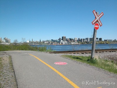 Bicycle path crossing train tracks with the city skyline of Ottawa,