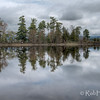 """The point, with a thin line of trees, extends into the middle of the Ottawa River. Glasslike reflections on a windless morning. Pinhey's Point Heritage Property and Park.  <a href=""""http://www.gettyimages.ca/detail/photo/pinheys-point-heritage-property-and-park-royalty-free-image/166549519"""" target=""""_blank"""">License this photo on Getty Images</a> © Rob Huntley2012"""
