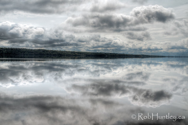 The Quebec shore and cloud reflections viewed from the Ontario side of the Ottawa River at Pinhey's Point Heritage Property and Park. © Rob Huntley 2012