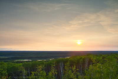 The sun setting over the forest of Prince Albert National Park.