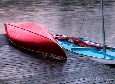 Red canoe on the dock. Red canoe on a cottage dock on Big Cedar Lake near Messines, Quebec.  HDR. Movement of sailboat between exposures caused slight ghosting blur of mast and ropes.  © Rob Huntley