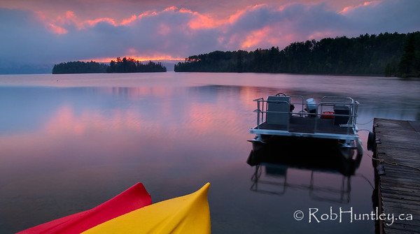 Sunset after the Storm. The sun goes down on a quiet evening after a storm on Big Cedar Lake near Messines, Quebec.  © Rob Huntley
