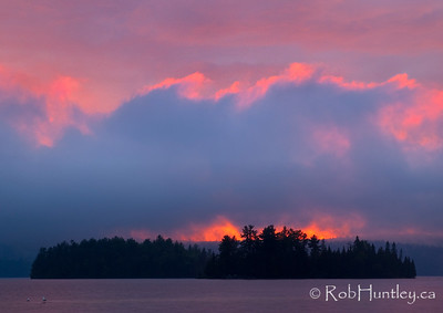 Big Cedar Lake Island at Sunset. After a storm had passed through, dark clouds are backlit by the fiery sunset. Island in Big Cedar Lake near Messines, Quebec. Seagulls standing on a shoal.  © Rob Huntley