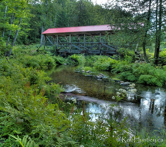 A covered bridge over a stream that connects Big Cedar Lake and Little Cedar Lake near Messines, Quebec.  © Rob Huntley